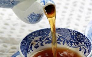 Schwarzer Tee wird in eine dekorative Teetasse gegossen