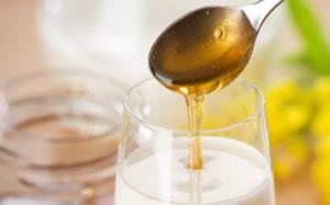 Ein Löffel Honig wird in ein Glas Milch gegeben