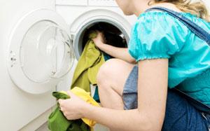 Eine Frau legt Wäsche in die Waschmaschine