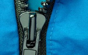 Ein geöffneter Reissverschluss von einer blauen Jacke