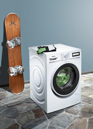 Hinter einer Waschmaschine steht ein Snowboard