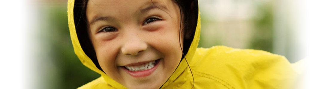 Mädchen trägt einen gelben Regenmantel