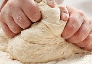 Kinderhände kneten einen Teig