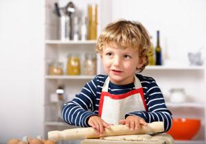 Ein blonder Junge rollt einen Teig aus