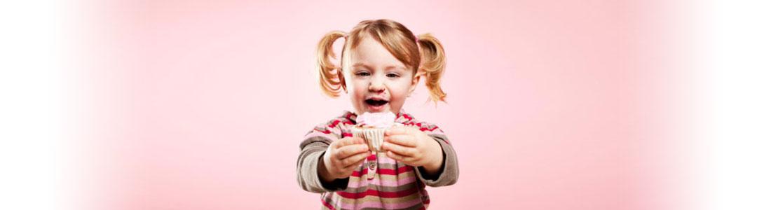 Ein kleines Mädchen hält einen Cupcake