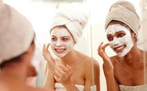 Zwei Frauen tragen eine weisse Gesichtsmaske auf