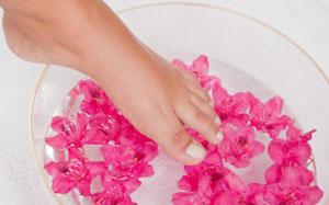 Ein Frauenfuss berührt ein Fussbad mit pinken Blüten
