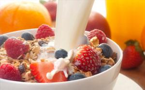 Milch wird über ein Obstmüsli gegeben
