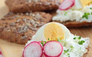 Körnerbrot mit einem Belag aus Frischkäse sowie Radieschen und hartgekochten Eiern