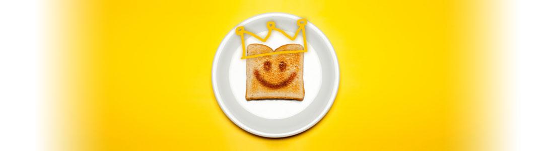 Eine Scheibe Toast mit einem lachenden Gesicht und einer Krone