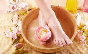 Frauenfüsse baden in einem Fussbad mit Blütendeko
