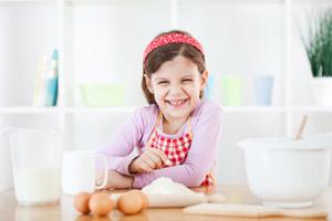 Ein Mädchen sitzt vor Backzutaten an einem Küchentisch