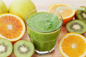 Ein grüner Smoothie im Glas mit aufgeschnittenem Obst drumherum
