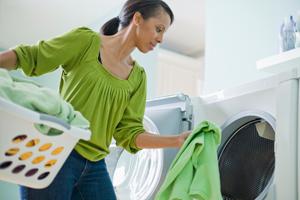 Une femme met du linge dans le sèche-linge