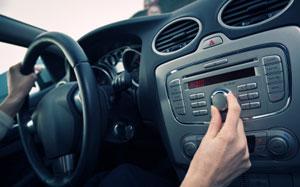 Eine Hand stellt einen Radiosender im Auto ein