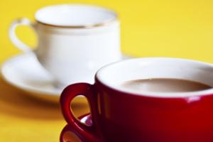 Eine rote und eine weisse Kaffeetasse stehen auf einem gelben Untergrund