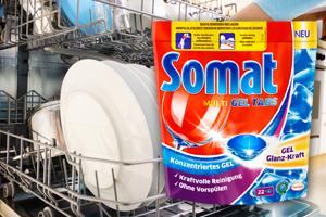 Ein Packung Somat steht neben einer offenen Geschirrspülmaschine