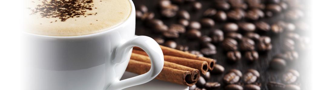Eine Tasse Kaffee, eine Zimtstange und Kaffeebohnen