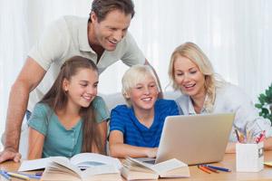 Eine Familie schaut zusammen auf einen Laptop