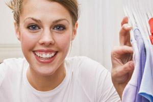 Eine junge Frau hat Kleidung auf Bügeln zur Seite geschoben und lächelt