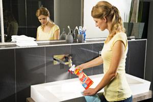 Eine Frau reinigt eine Waschbecken mit Bref Power Kalk & Schmutz