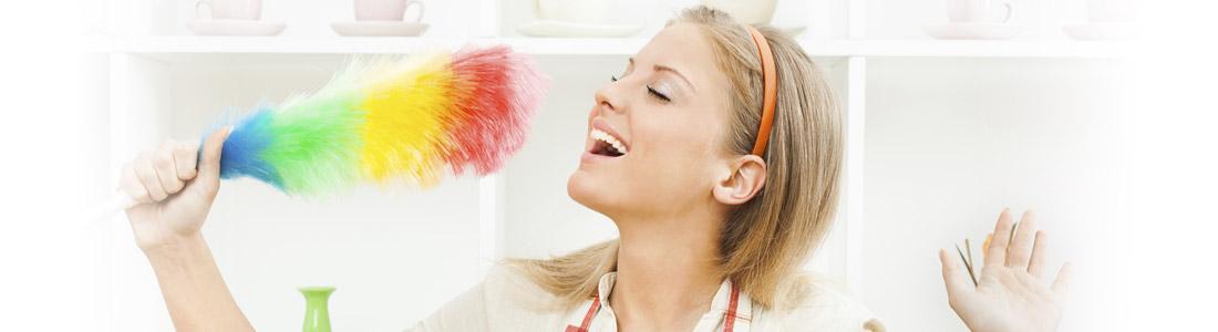 Frau benutzt einen Staubwedel als Mikrofon
