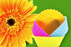 Une fleur de gerbera jaune se trouve à côté de moules à muffins colorés