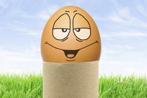 Ein Ei mit einem lustigen Gesicht steckt auf einer Papprolle