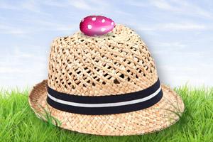 Ein pinkes Ei mit weissen Punkten liegt auf einem Herrenstrohhut