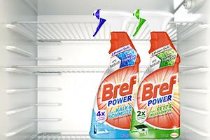 Eine Reinigerflasche steht vor einem offenen Kühlschrank