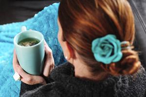 Une femme se réchauffe les mains sur une tasse de thé chaud