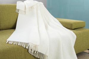 Une couverture blanche en laine est étendue sur un canapé vert