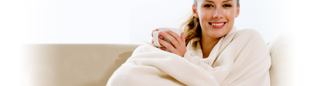 Eine Frau sitzt in einer Decke eingewickelt auf dem Sofa und hält eine Tasse in den Händen