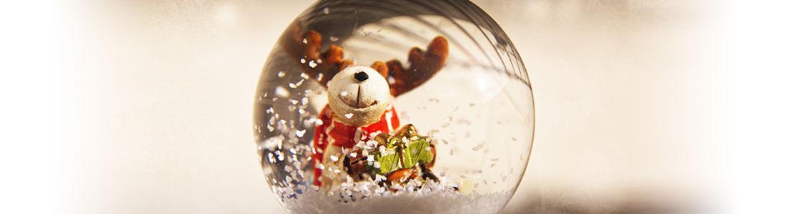 Eine weihnachtliche Schneekugel mit einem Rentier und Weihnachtsgeschenken