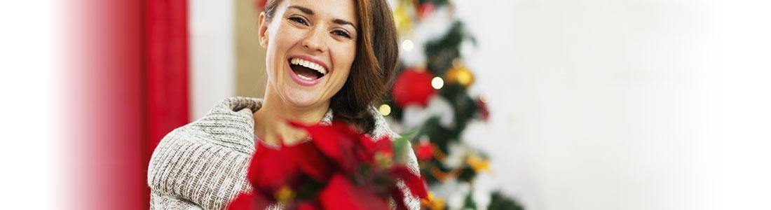 Eine Frau hält einen Weihnachtsstern in der Hand