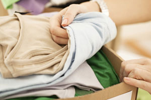 Frauenhände sortieren Kleidung zum Ausmisten von Keller oder Dachboden