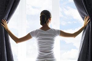 Frau öffnet Vorhänge am Fenster zum Lüften