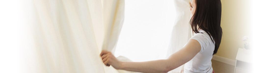 Frau öffnet Vorhänge zum Lüften