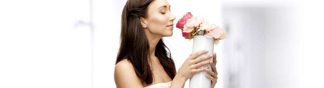Bastelidee Frau mit selbstgestalteter Vase riecht an Blumen