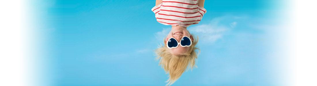Kind mit herzförmiger Sonnenbrille hängt kopfüber