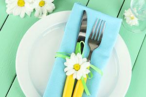 Tischdeko-Tipp für Brunch: Bunte Serviette mit Besteck zusammengehalten von Blume