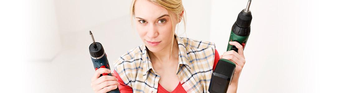 Frau mit Bohrer befolgt Heimwerker-Tipps in ihrem Haushalt