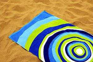 Buntes Strandtuch aus Strandtasche im Sand