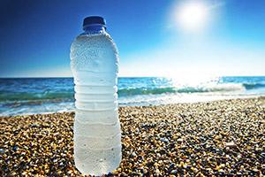 Kalte Wasserflasche aus Strandtasche am Strand
