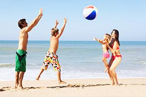 Eltern und Kinder spielen mit Wasserball aus Strandtasche