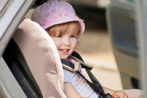 Kind im Kindersitz mit Schutzbezug gegen Flecken
