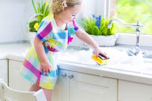 Kind entfernt Flecken auf der Spüle