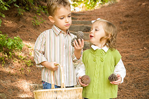Kinderspiele im Herbst: Kinder sammeln Tannenzapfen