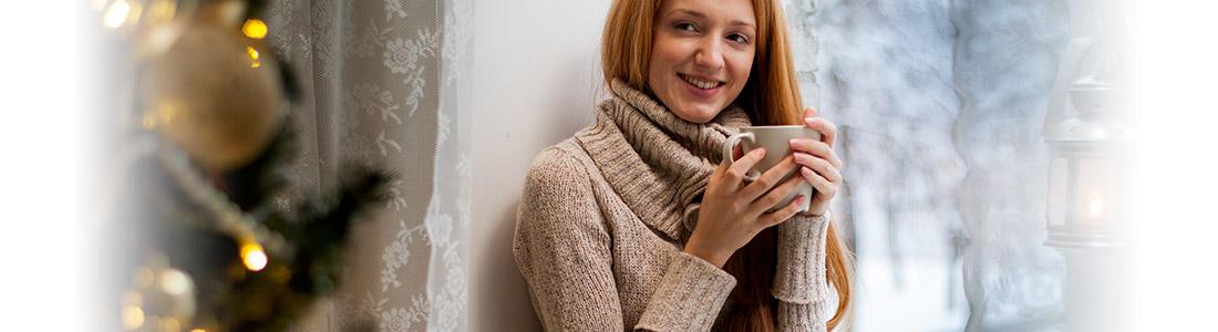 Frau mit Tasse entspannt an Weihnachten