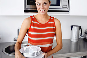 Frau räumt Geschirr auf nach Party